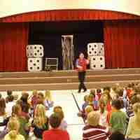Presto the magician performs at an elementary school assembly program