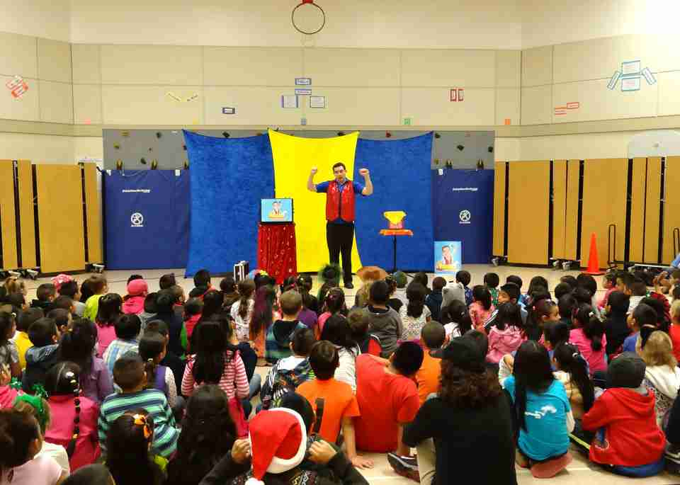 Presto performs comedy magic for an elementary school audience